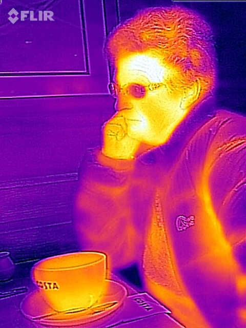 My wife, sat drinking coffee, and wearing a quilted jacket.