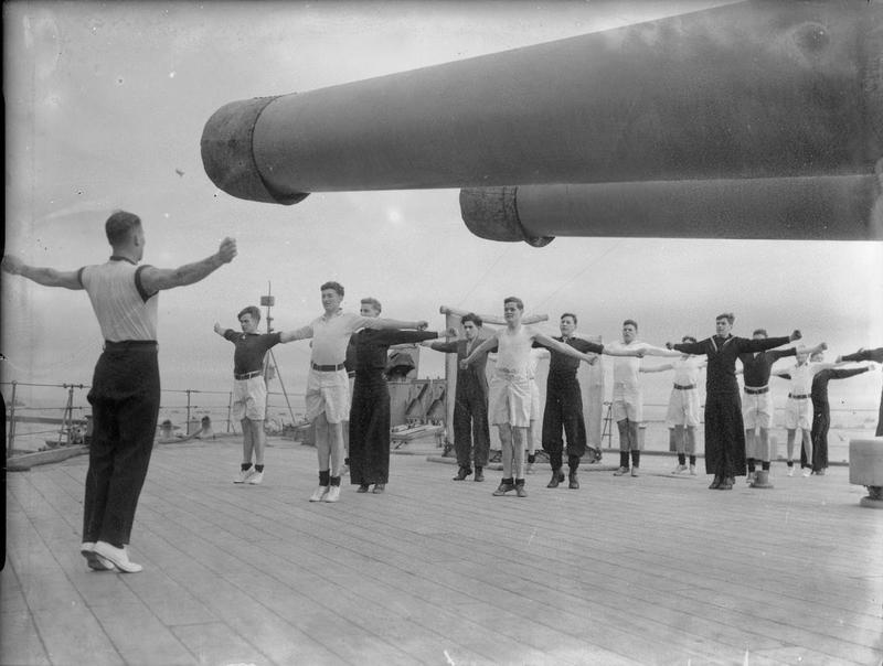 Part of the Boys' Division at physical training, exercising beneath the 15 inch guns of HMS Malaya, during the Second World War. Photo by Lt C H Parnall, released courtesy of the Imperial War Museum (photo A 5690), via Wikimedia Commons.